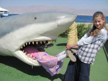 eilat holidays - girl climbing into shark model in the playground of the Eilat underwater observatory
